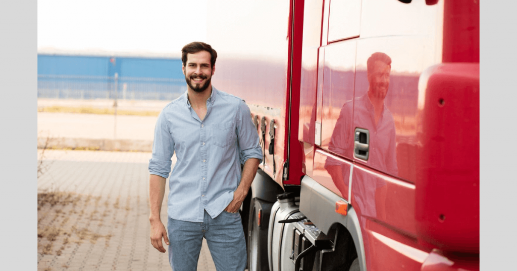 A happy and smiling HGV driver standing by his red truck
