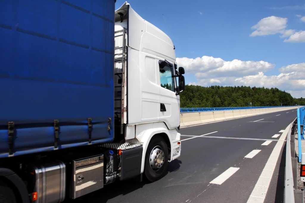 A white and blue HGV truck driving on the motorway