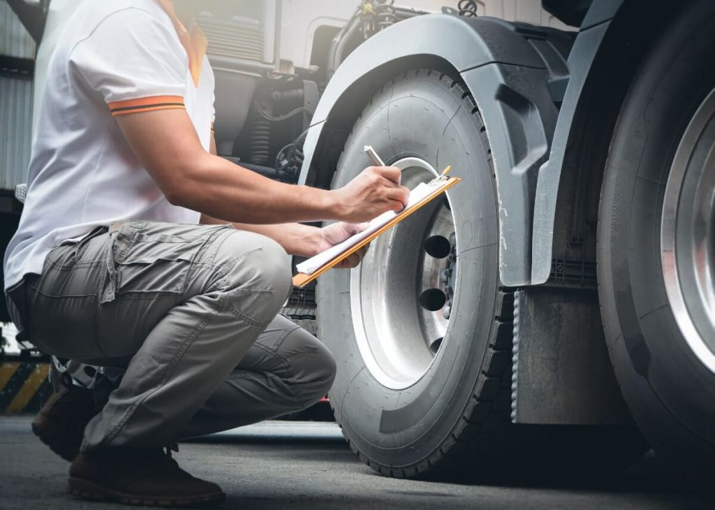 A driver is checking the tyres on the HGV lorry