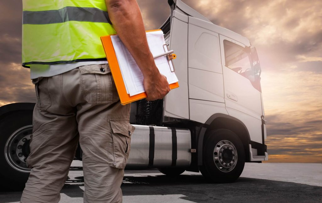 A HGV driver is standing next to his truck with a daily walkaround checks clipboard
