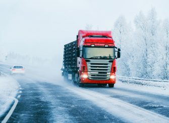A red HGV truck driving on a snowy road in winter